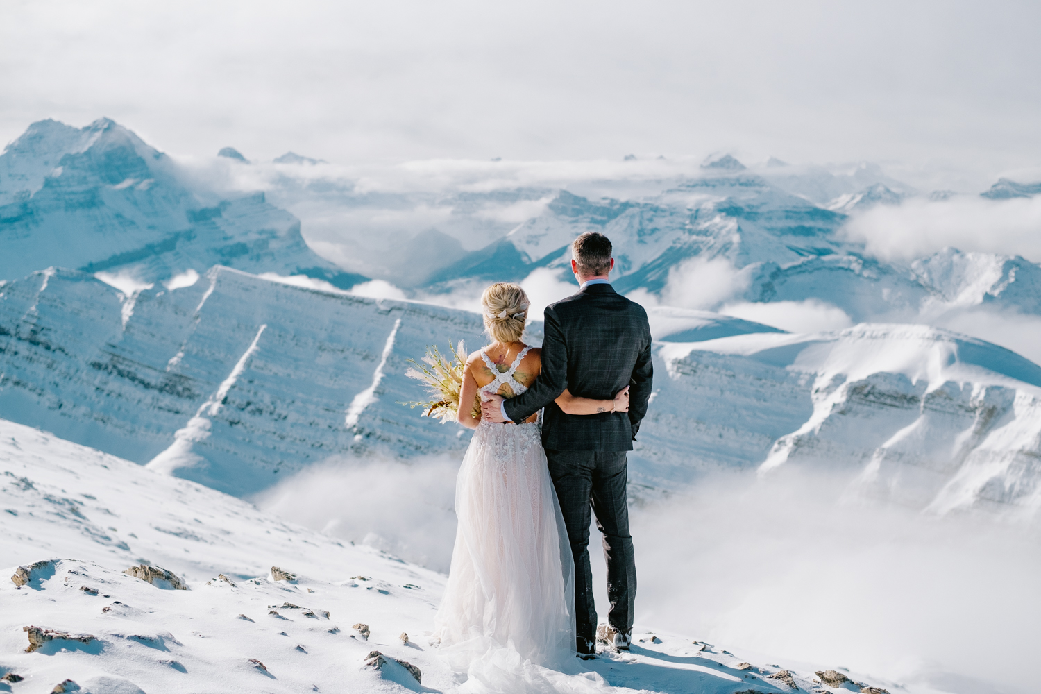 bride and groom enjoying mountain top views in Banff