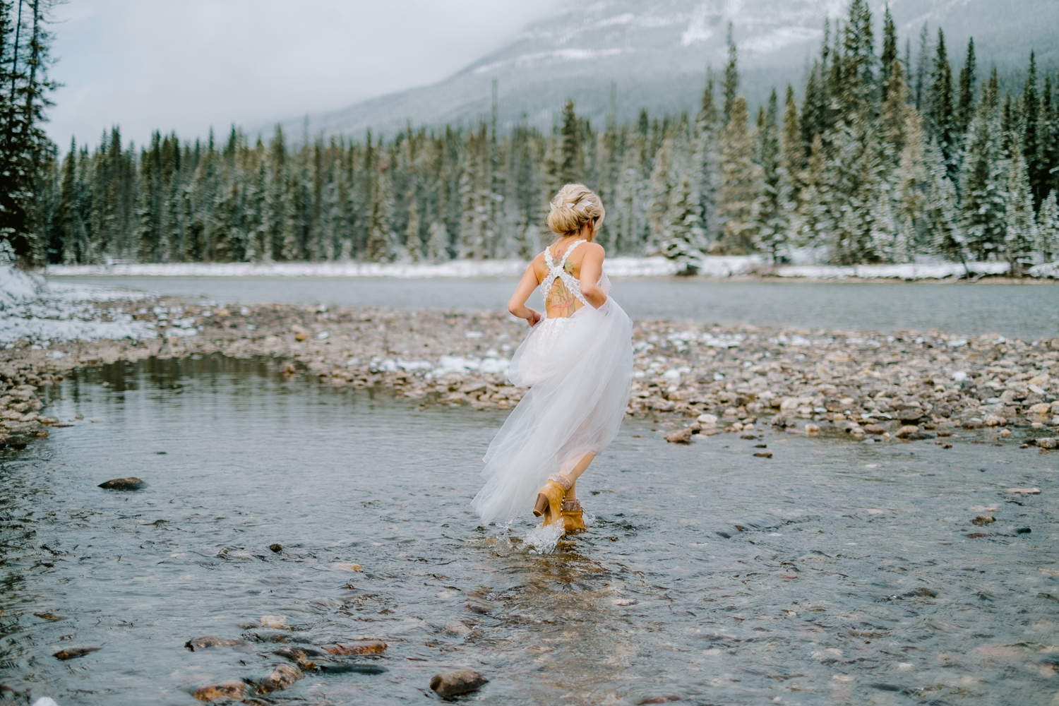 Banff Bride crossing river in unique wedding dress
