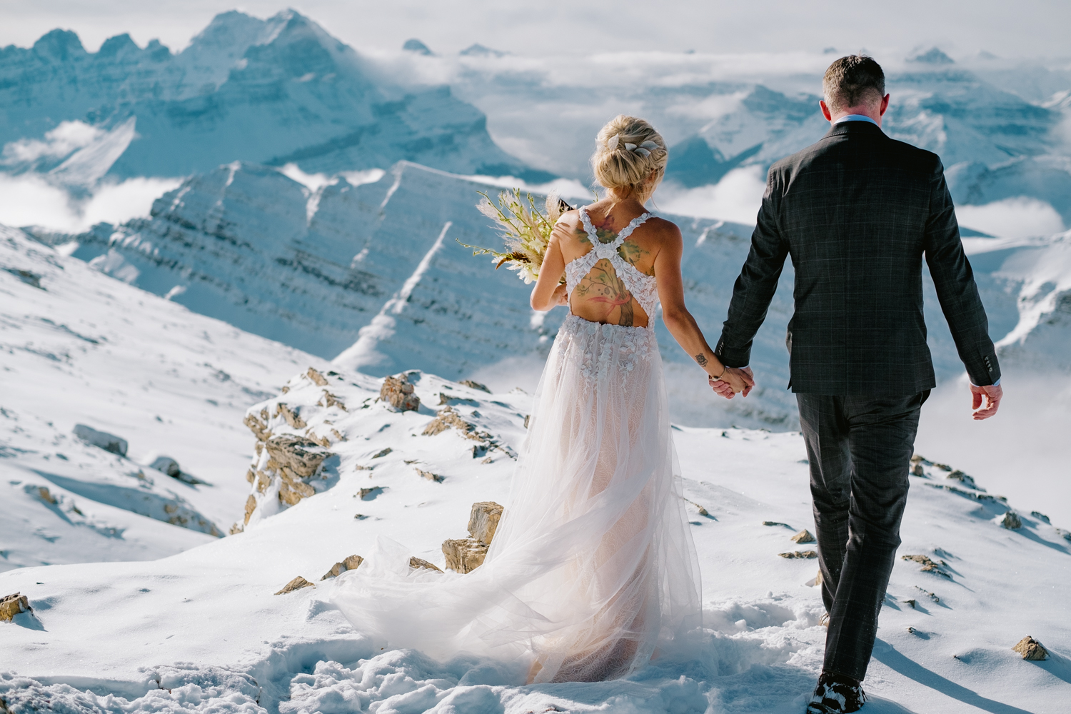 Bride and Groom walking on mountain top in Banff in winter